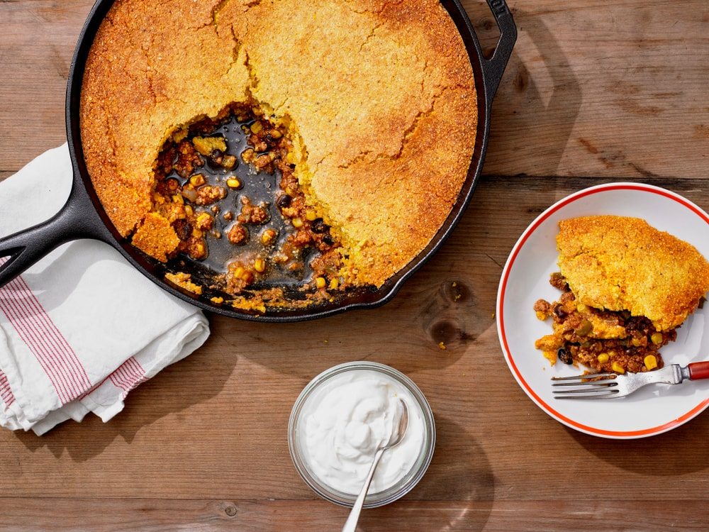 Mexican cornbread casserole in a skillet pan and a small dish beside a dip on a wooden background.