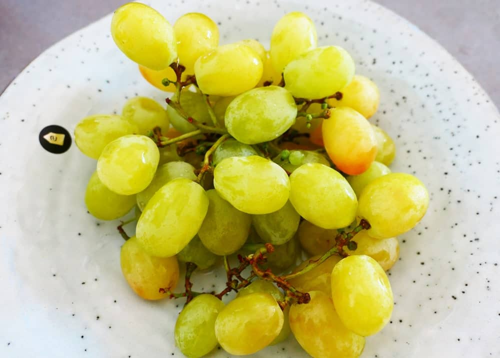 Cotton candy grapes on a ceramic plate.