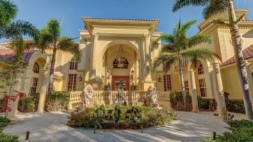 This is the front view of the house with a sunny yellow tone to its exterior walls adorned by the tall tropical trees and a miniature garden by the entrance with a large archway. Image courtesy of Toptenrealestatedeals.com.
