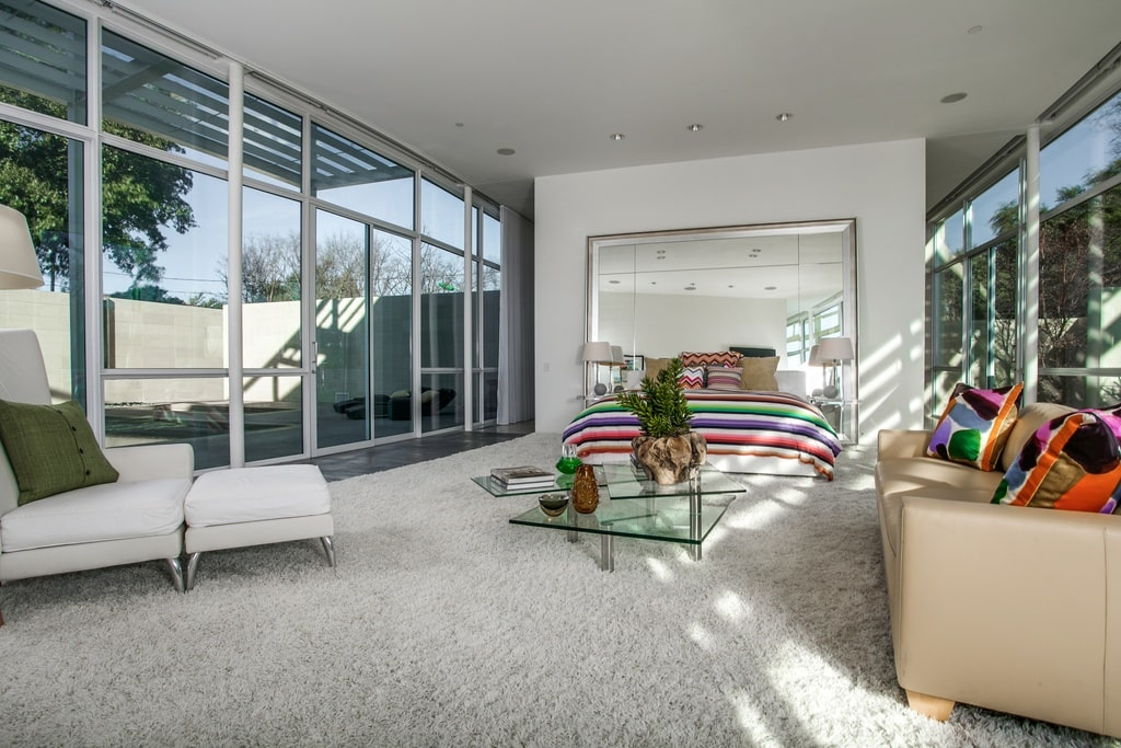 The primary bedroom of the house also has glass walls that bring in natural lighting fro the gray floor, walls and ceiling. These are then complemented by the colorful patterned sheets of the bed on the far side. Image courtesy of Toptenrealestatedeals.com.