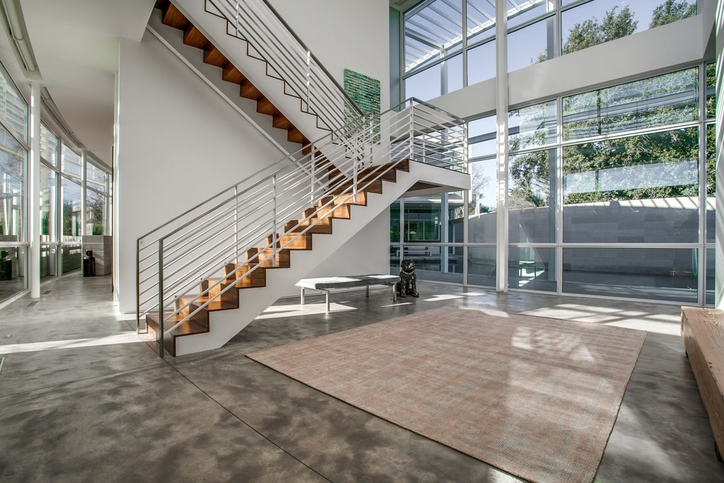This is the spacious and airy foyer with tall glass walls to bring in natural lighting. You can also see here the staircase on the side. Image courtesy of Toptenrealestatedeals.com.