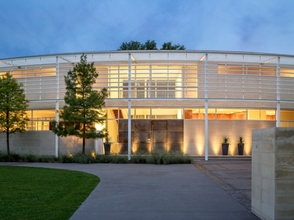 This is the front of the contemporary-style house. You can see its bright white exteriors complemented by the warm lighting and the landscaping that has shrubs and a tall tree. Image courtesy of Toptenrealestatedeals.com.
