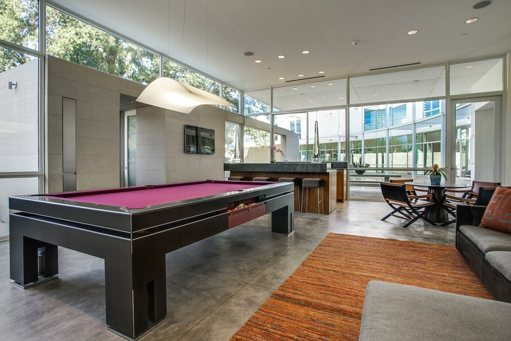 This is a look at the game room of the house. It has a large black pool table with contrasting red carpet surface. Image courtesy of Toptenrealestatedeals.com.