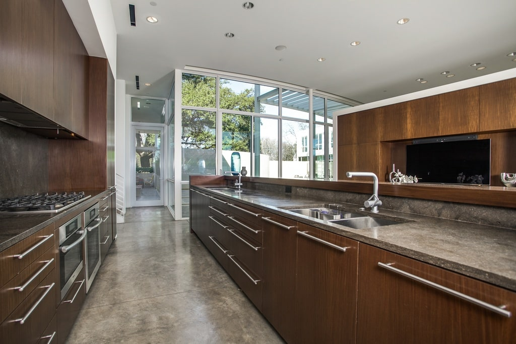 This is a look at the kitchen that has a large kitchen island with dark brown wooden cabinetry that stands out against the gray concrete flooring that matches the countertops. Image courtesy of Toptenrealestatedeals.com.