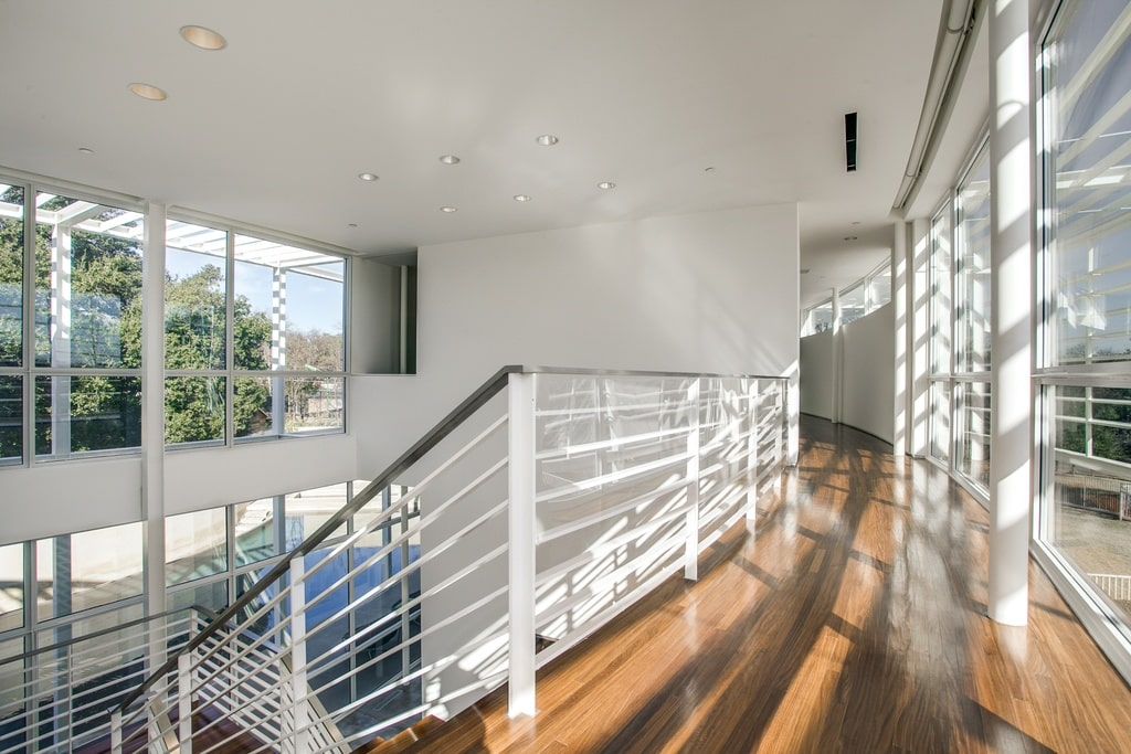This is the second-floor landing with hardwood flooring and white railings to its indoor balcony that looks over the foyer. Image courtesy of Toptenrealestatedeals.com.