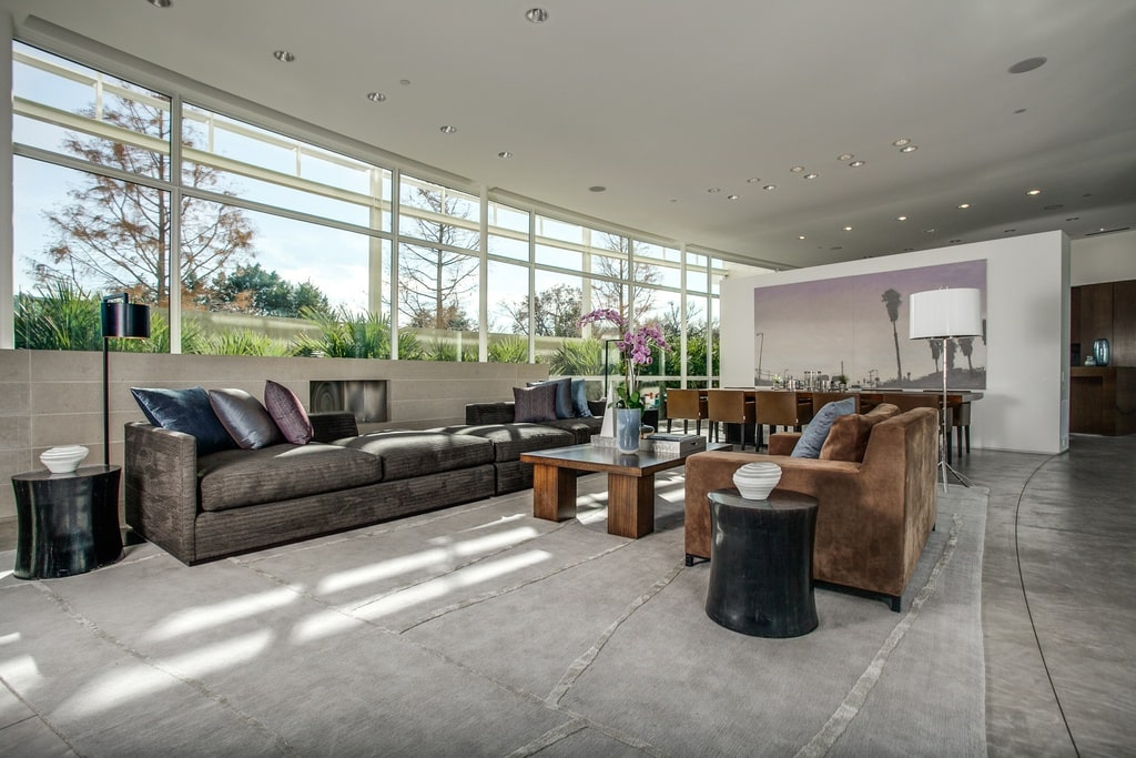 This is the living room area with a large row of glass walls above the low wall that houses the modern fireplace across from the gray sofa. You can also see the dining area on the far side. Image courtesy of Toptenrealestatedeals.com.