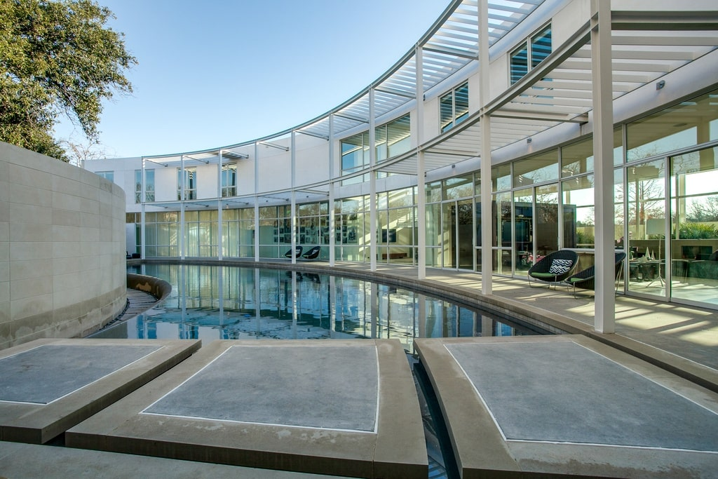 This is a view of the contemporary-style house with glass walls, that look over the curved infinity edge pool.