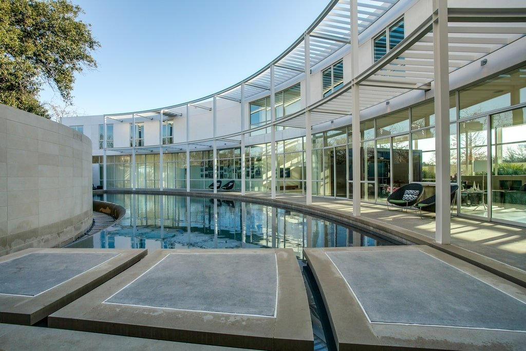 This is a view of the contemporary-style house with glass walls, that look over the curved infinity edge pool. Image courtesy of Toptenrealestatedeals.com.