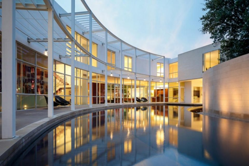 This is the view of the vurved contemporary house from the other end of the infinity edge pool. This also shows the warm glow of the interiors that escape onto the pool through glass walls. Image courtesy of Toptenrealestatedeals.com.