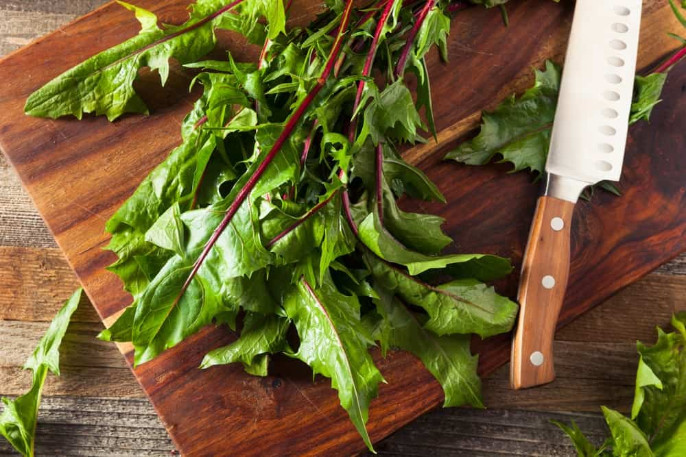 Dandelion greens and a knife on a wooden chopping board.