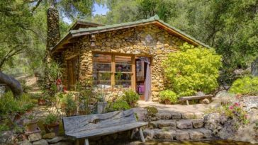 This is a look at one of the cottages of the property with stone exterior walls complemented by the surrounding landscape with trees, shrubs, stone steps and a wooden bench. Image courtesy of Toptenrealestatedeals.com.