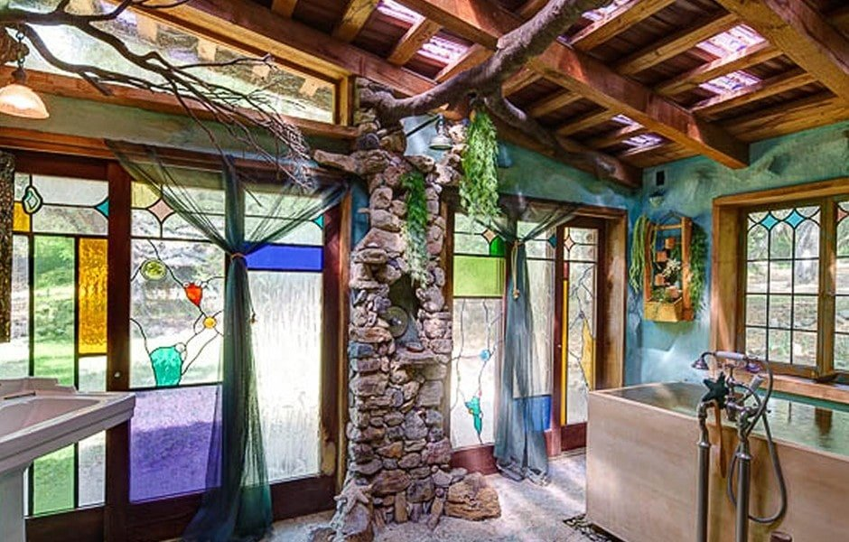 This is a look at the bathroom with a wooden shed ceiling, panels of stained glass and a large Japanese soaking tub. Image courtesy of Toptenrealestatedeals.com.