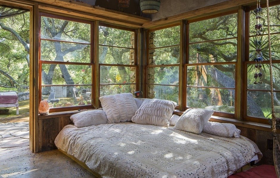 This is a close look at the bedroom with a comfortable platform bed placed at the corner by the large glass windows with a view of treetops. Image courtesy of Toptenrealestatedeals.com.