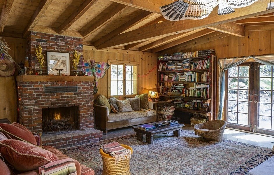 This living room has a large red brick fireplace, a large sofa and a large wooden bookshelf on the side. Image courtesy of Toptenrealestatedeals.com.