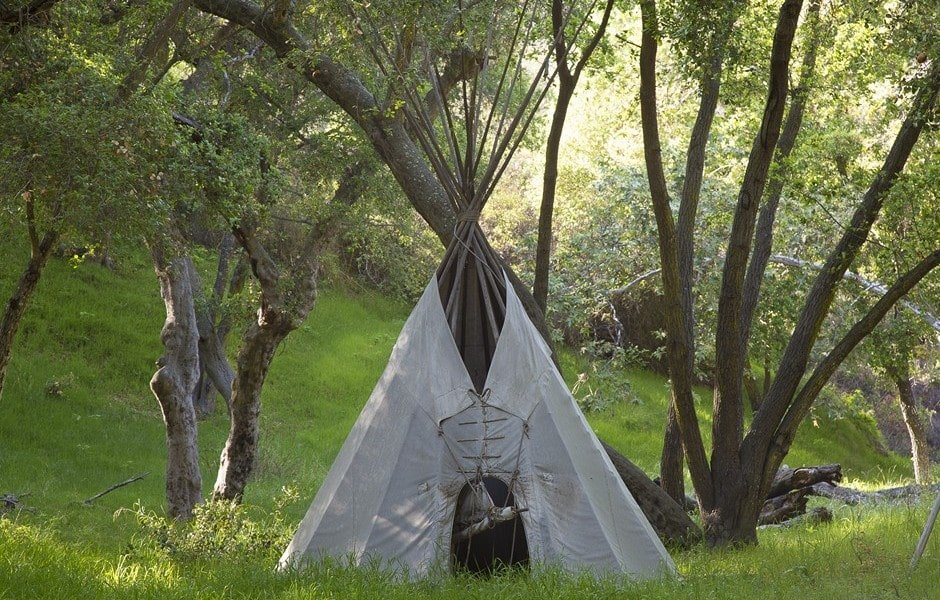At a corner of the property is this large Native American Tipi tent beside tall trees. Image courtesy of Toptenrealestatedeals.com.