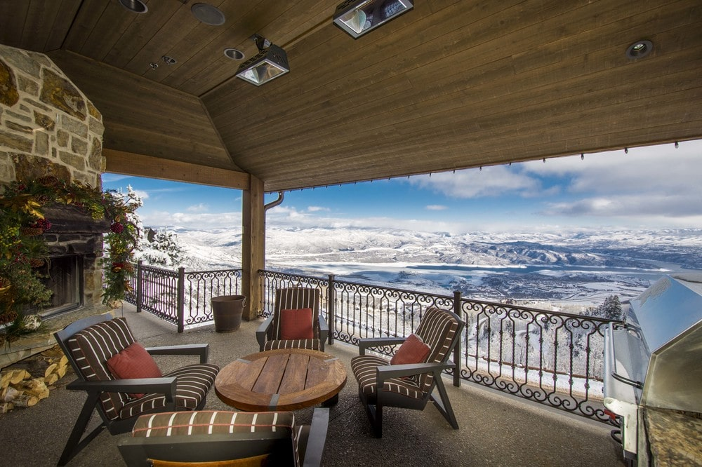 This is the balcony fitted with outdoor chairs surrounding a round coffee table to better enjoy the sweeping view of the mountains. Image courtesy of Toptenrealestatedeals.com.