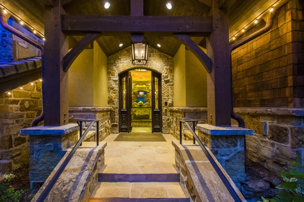 This other look at the main entrance shows the main door topped with a warm pendant light over the arch. Image courtesy of Toptenrealestatedeals.com.