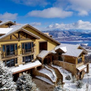 This is an aerial view of the front of the house showcasing the frozen landscape with tall trees and a sweeping view of the mountains. Image courtesy of Toptenrealestatedeals.com.