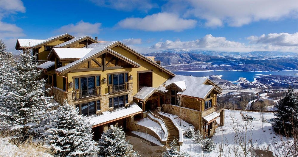 This is an aerial view of the front of the house showcasing the frozen landscape with tall trees and a sweeping view of the mountains. These make the earthy exterior walls and glass walls of the house stand out. Image courtesy of Toptenrealestatedeals.com.
