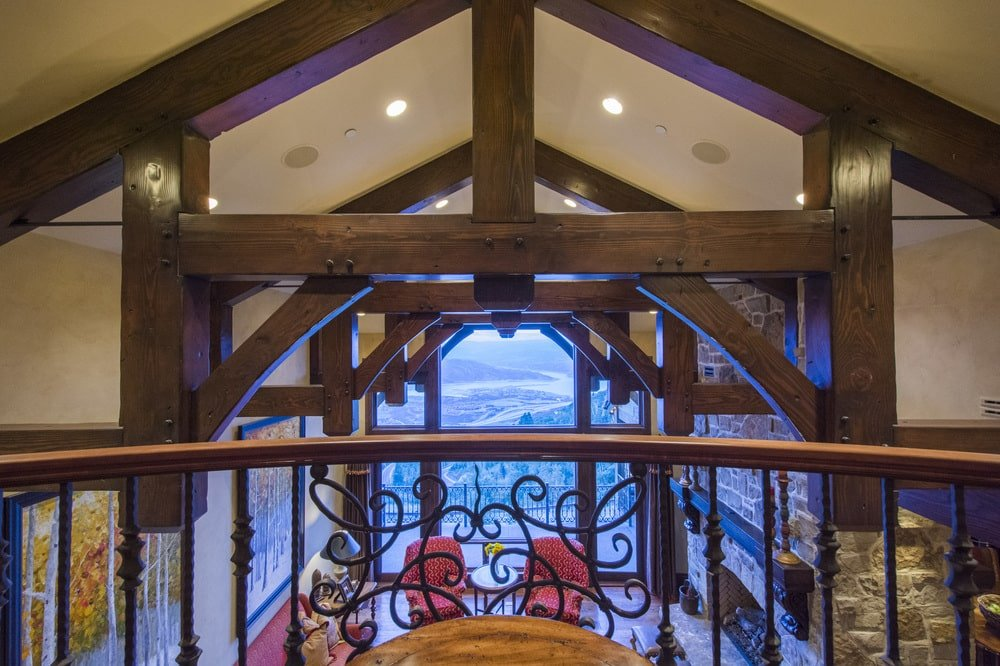 This is a look at the large room below from the vantage of the indoor balcony that has wrought-iron railings and wooden banisters. Image courtesy of Toptenrealestatedeals.com.