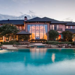 This is a view of the back of the mansion where you can see the massive glass wall glowing from interior lights. This is adorned with tall trees and shrubs from the landscaping. Image courtesy of Toptenrealestatedeals.com.