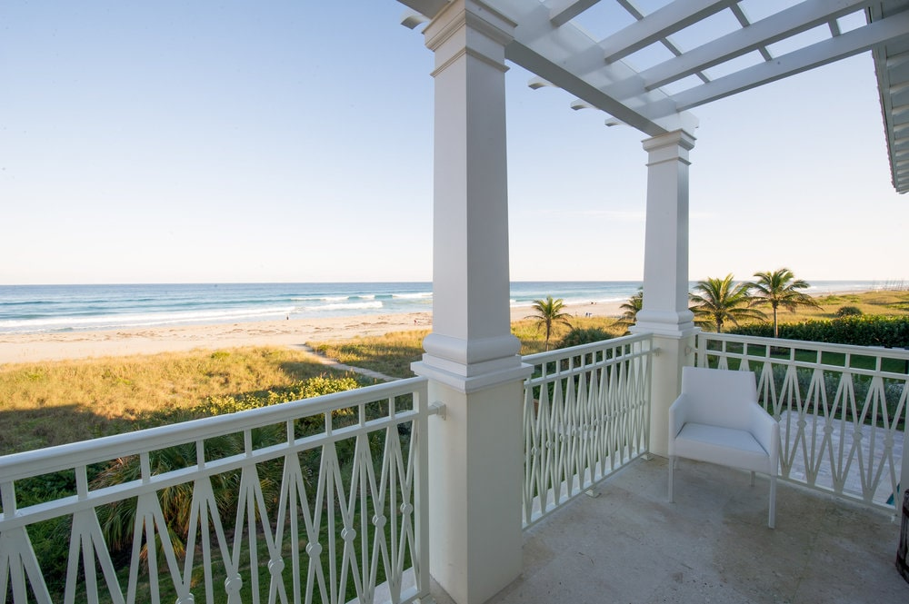 This is a look at the sweeping views of the ocean from the vantage of the second-floor balcony that has railings and pillars of the same tone. Image courtesy of Toptenrealestatedeals.com.