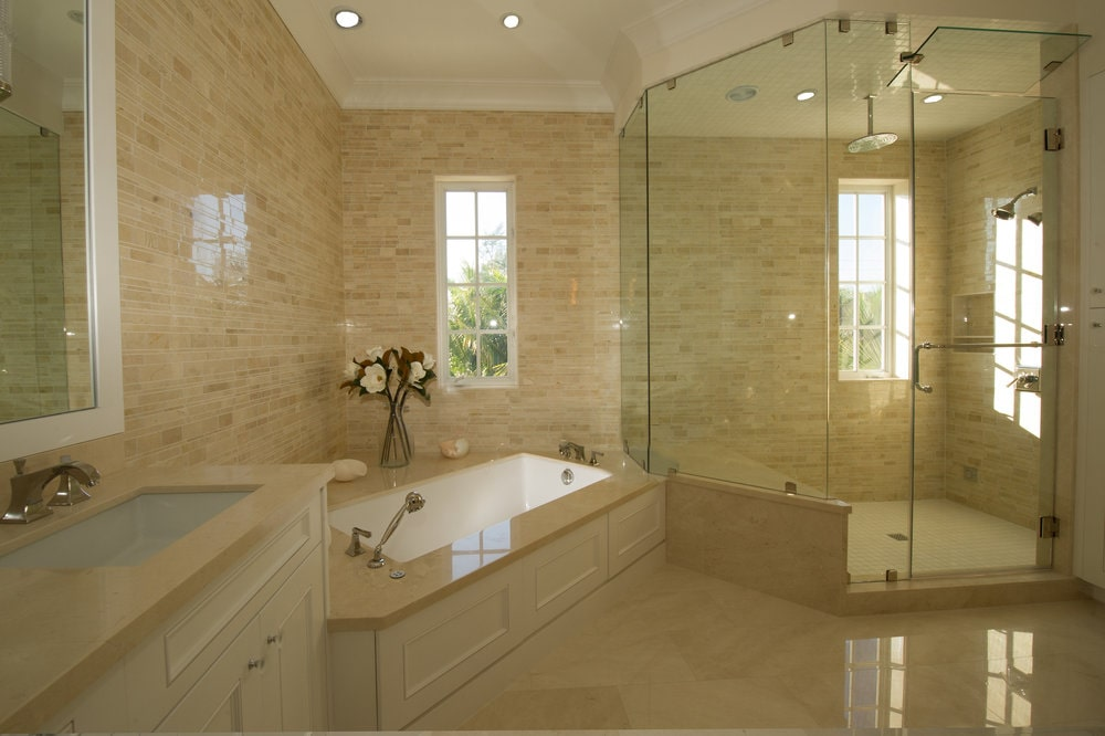 The bathroom has a consistent beige tone to its walls, floor and ceiling. On one corner is the bathtub and on the side of it is the glass-enclosed shower area. Image courtesy of Toptenrealestatedeals.com.