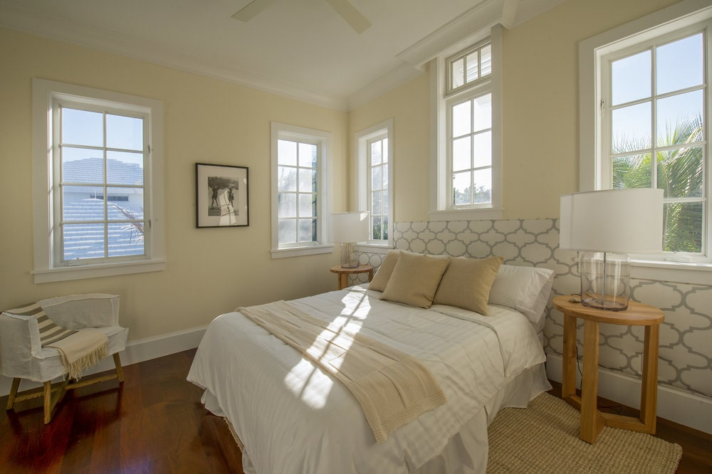 The bedroom has a beige bed with a cushioned headboard. This is flanked by bedside tables with lamps. Image courtesy of Toptenrealestatedeals.com.