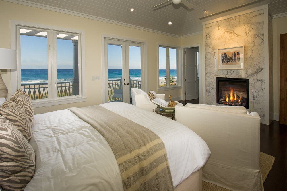 This other view of the bedroom shows the stone fireplace across from the foot of the bed where there is a comfortable armchair. Image courtesy of Toptenrealestatedeals.com.