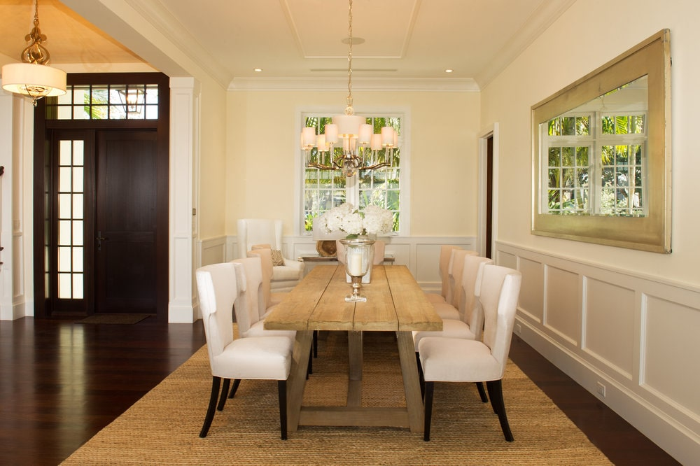 A few steps from the foyer is this formal dining room with white wainscoting to match the cushioned chairs of the rectangular dining table. Image courtesy of Toptenrealestatedeals.com.