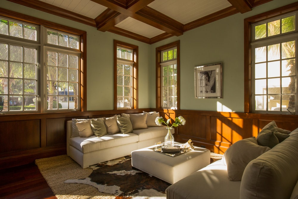 This family room has beige sofas paired with a beige cushioned coffee table. These are then complemented by the surrounding wooden wainscoting that matches the window frames and ceiling coffers. Image courtesy of Toptenrealestatedeals.com.