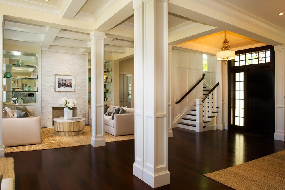 The foyer has a black main door adorned with small glass panels. The dark hardwood flooring of the foyer is contrasted by the white pillars standing on each side. Image courtesy of Toptenrealestatedeals.com.