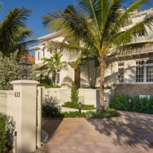 This is the front view of the house with warm beige exterior walls adorned by tall tropical trees and various shrubberies lining the sides of the house. Image courtesy of Toptenrealestatedeals.com.