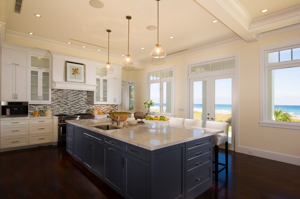The dark wooden tone of the kitchen island blends well with the dark hardwood flooring. These are then contrasted by the light tones of the countertops, walls and ceiling. Image courtesy of Toptenrealestatedeals.com.