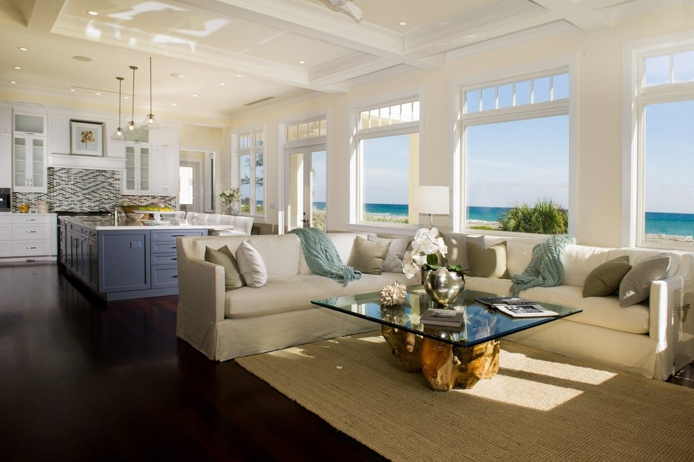 This living room has a glass-top coffee table paired with a large L-shaped sectional sofa. Image courtesy of Toptenrealestatedeals.com.