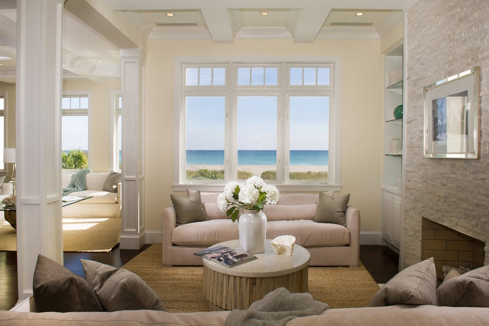 This other living room has a couple of beige sofas flanking a coffee table across from the fireplace. Image courtesy of Toptenrealestatedeals.com.