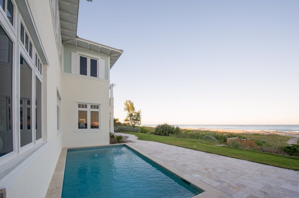 This is the swimming pool at the back of the house surrounded by concrete walkways on one side and the house exterior walls on the other. This pool has a sweeping view of the beach and the ocean beyond. Image courtesy of Toptenrealestatedeals.com.