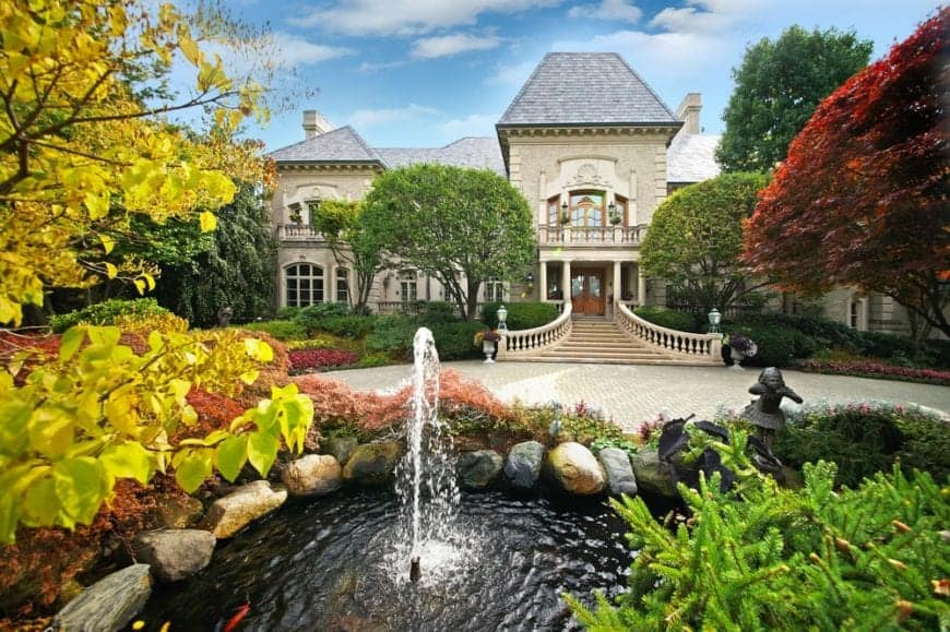 This is an aerial view of the front of the house that is complemented by the surrounding landscape of tall trees, colorful shrubs and a pond with a fountain across from the large courtyard of the main entrance.