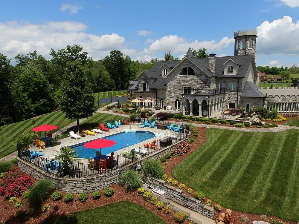 This is a view of the manor from the back. Here you can see the large swimming pool flanked with grass lawns. This also gives a view of the gray stone castle with a turret, <a class=