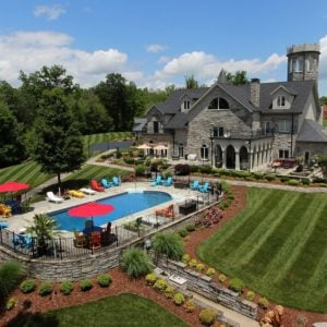 This is a view of the manor from the back. Here you can see the large swimming pool flanked with grass lawns. This also gives a view of the gray stone castle with a turret, dormer windows and arches. Image courtesy of Toptenrealestatedeals.com.