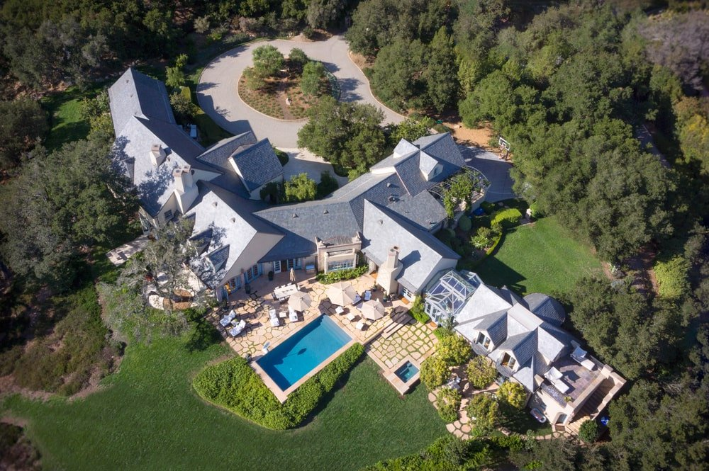 This is an aerial view of the whole estate showing the driveway, landscaping of trees and the pool area at the back next to a large grass lawn. Image courtesy of Toptenrealestatedeals.com.