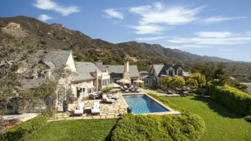 This is a back view of the estate showing an earthy beige tone to the exterior walls that extend to the mosaic stone walkways of the pool area. These are complemented by the surrounding green landscape of grass and shrubs. Image courtesy of Toptenrealestatedeals.com.