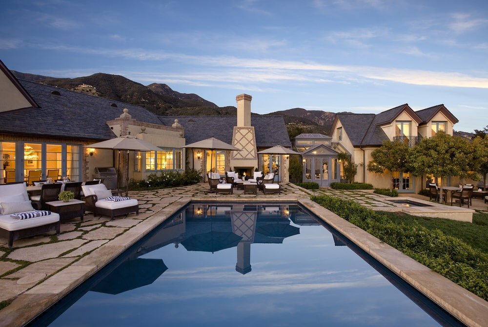 This is a view of the house from the vantage of the pool. This shows the warm glow of the windows coming from interior lights that give the beige exterior walls of the house a homey feeling. Image courtesy of Toptenrealestatedeals.com.