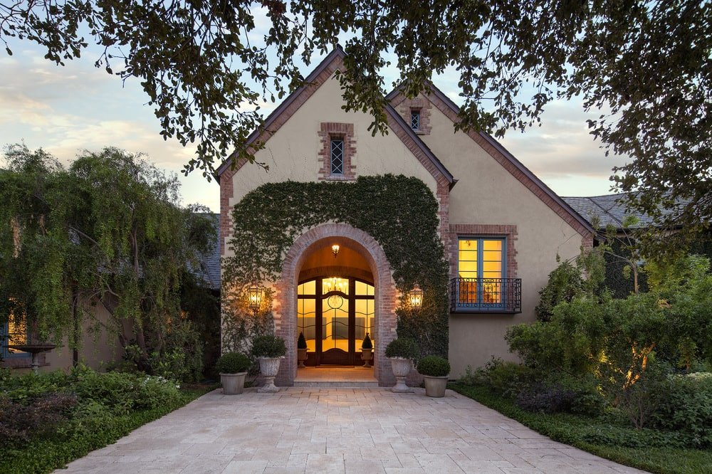 This is a look at the two-level guest house of the estate with light beige exterior walls adorned by the landscape. You can see here the main entrance that has an arched entryway and a warm glow. Image courtesy of Toptenrealestatedeals.com.