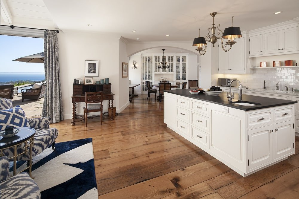 This other view of the kicthen shows its proximity to the living room as well as a work area on the side with a dark wooden desk that matches the hardwood flooring. Image courtesy of Toptenrealestatedeals.com.