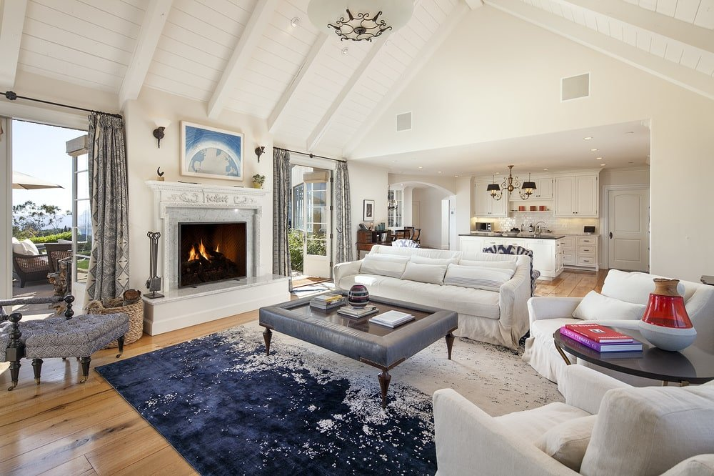 The living room has a fireplace embedded into the beige wall that matches with the tall arched ceiling. These aso match with the sofa set surrounding a glass-top coffee table on a colorful area rug. Image courtesy of Toptenrealestatedeals.com.