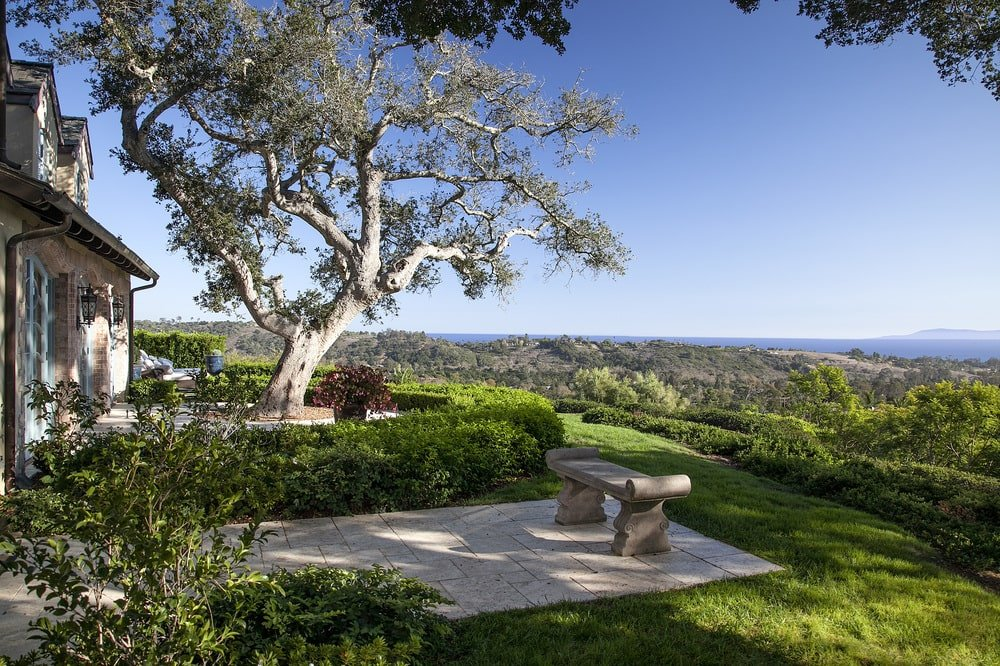 This is a look at a patio with a sweeping view of the forest below. This area is fitted with a built-in stone bench and adorned with well-manicured shrubs and trees. Image courtesy of Toptenrealestatedeals.com.