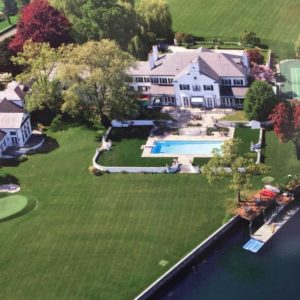 This is an aerial view of the mansion that stands out against the green lawns and tall trees surrounding the light-toned exterior walls. Image courtesy of Toptenrealestatedeals.com.