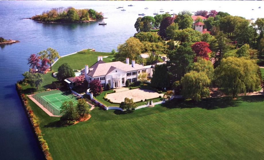 This is an aerial view of the mansion showcasing the light beige tone of the house exteriors making it stand out against the surrounding landscape of trees, shrubs and grass lawns. Image courtesy of Toptenrealestatedeals.com.