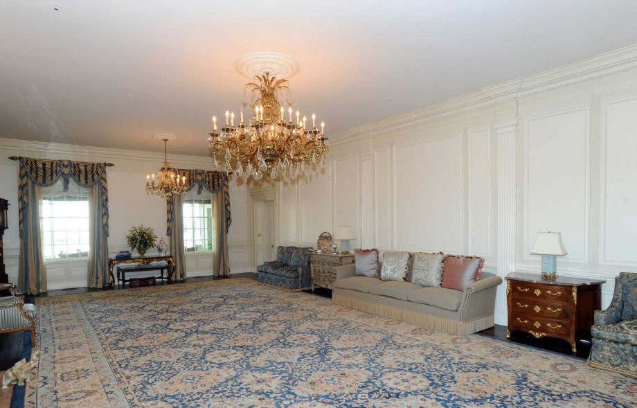 The family room has a spacious open area fitted with a floral patterned area rug that alsmost covers the whole floor. On the side against the wall is a sofa and in the middle of the room hangs a large chandelier. Image courtesy of Toptenrealestatedeals.com.